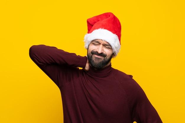 Mens met kerstmishoed over geïsoleerde gele muur met halspijn