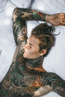 Mens met kleurrijke tatoegeringen die op een wit blad stellen