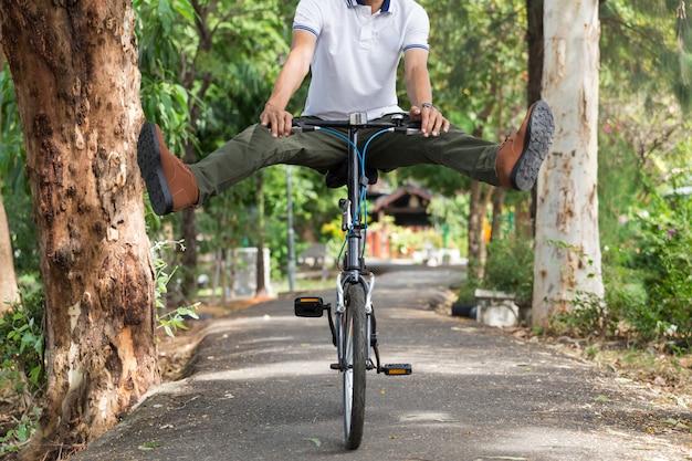Mens met ladingsbroek die een fiets in de tuin berijden