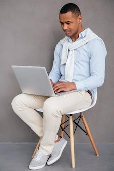 Mens met laptop. zelfverzekerde jonge afrikaanse man zittend op de stoel en werken op laptop