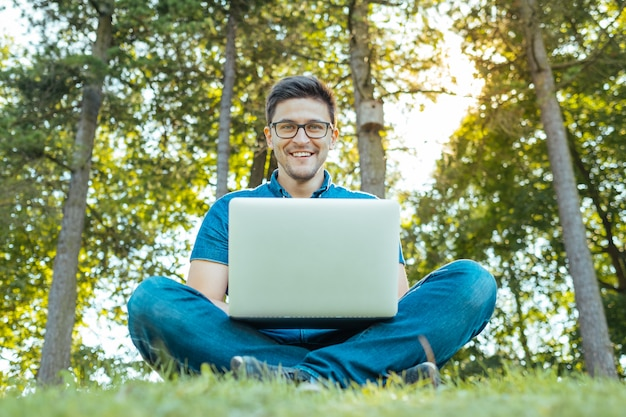 Mens met laptop zitting in openlucht in aard