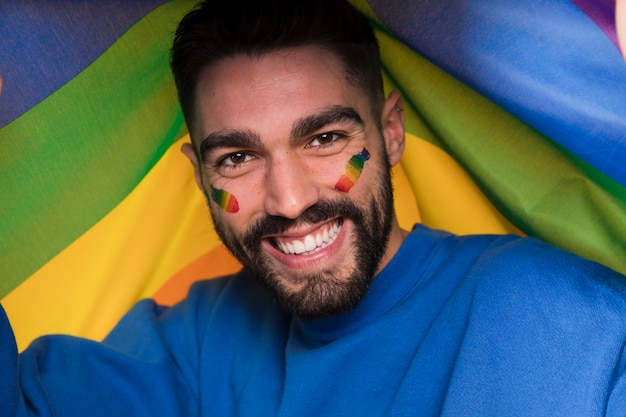 Mens met lgbt-regenboog op gezicht op vrolijke parade