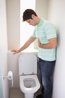 Mens met maagziekte ongeveer om in het toilet over te geven