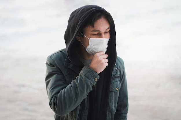 Mens met medisch masker dat buiten stelt