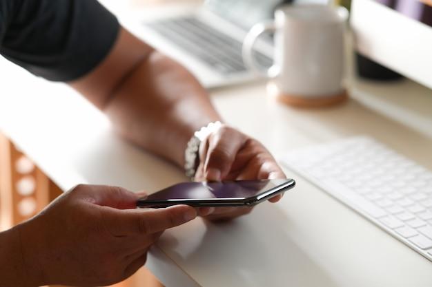 Mens met mobiele slimme telefoon op werkend bureau