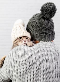 Mens met rug die klein katje houdt