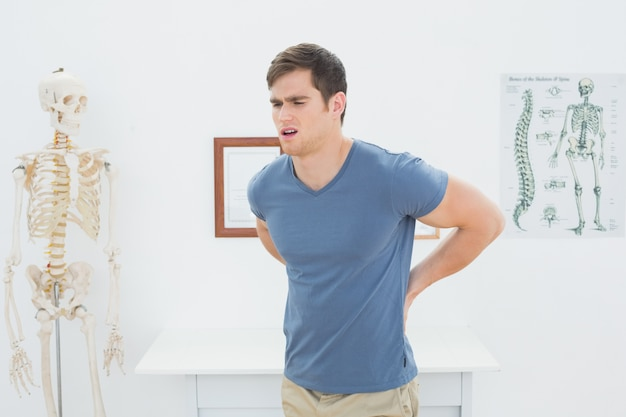 Mens met rugpijn in medisch kantoor