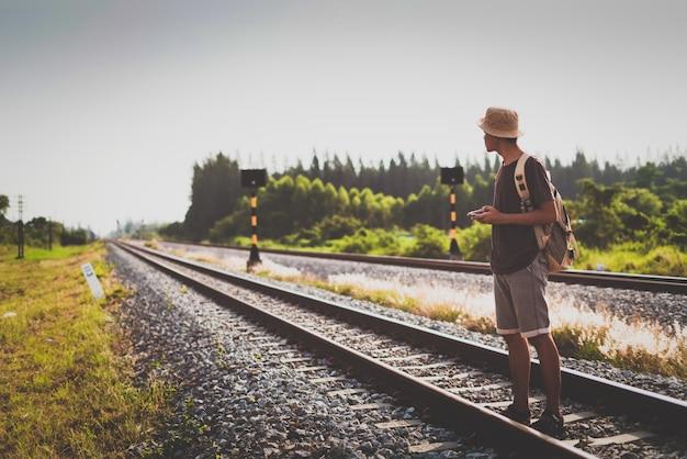 Mens met rugzak die op spoorweg weggaan en aan geduld benadrukken en smartphoneonderzoek gebruiken die stap vooruit naar doel proberen.