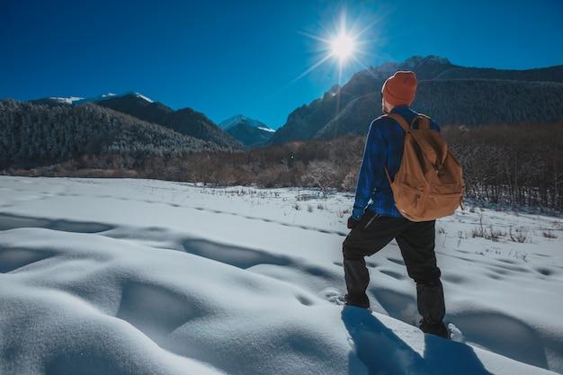 Mens met rugzaktrekking in bergen. koud weer, sneeuw op heuvels. winterwandelen. zon en sneeuw