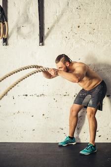 Mens met slagkabels die in geschiktheidsgymnastiek uitoefenen