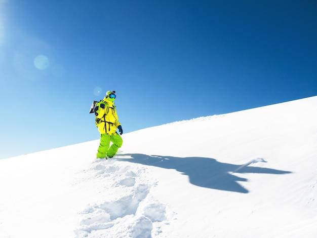 Mens met snowboard die in sneeuw bij hemelachtergrond blijft