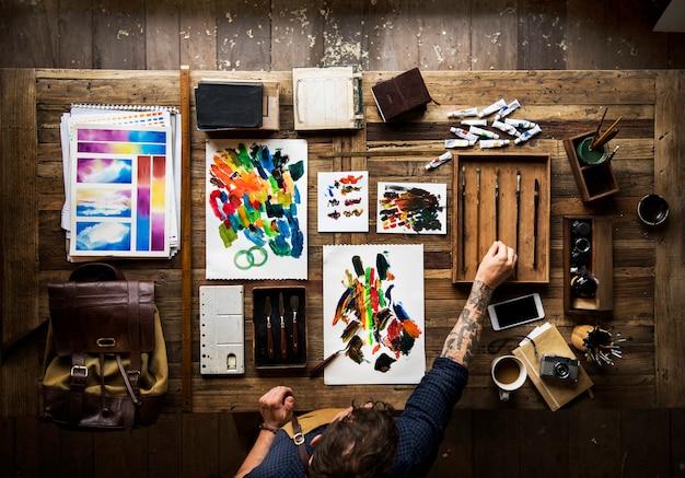 Mens met tatoegering op zijn handen die het schilderen doen
