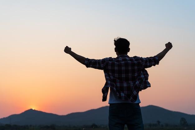 Mens met vuist in de lucht tijdens zonsondergang, gemotiveerd voelen, vrijheidsconcept.