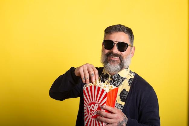 Mens met witte baard en zonnebril op gele achtergrond die popcorn het glimlachen eet. de emoties van mensen in het bioscoopconcept. film kijken, met een emmer popcorn.