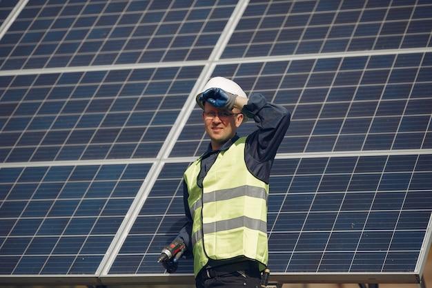 Mens met witte helm dichtbij een zonnepaneel