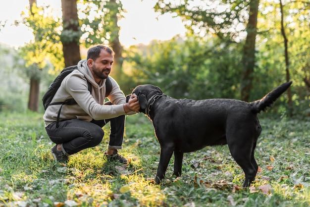 Mens met zijn het zwarte spelen van labrador in tuin op groen gras
