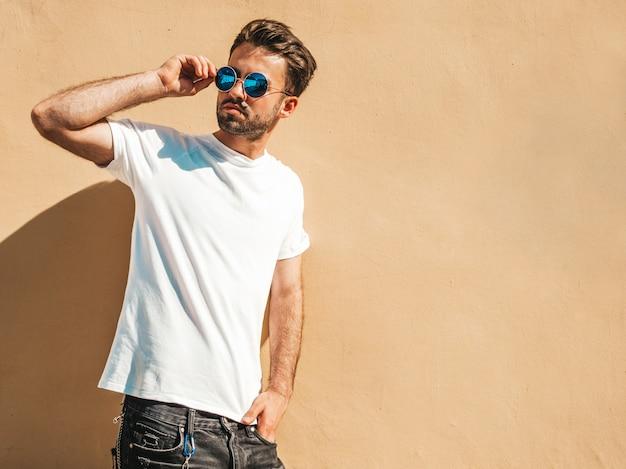 Mens met zonnebril die het witte t-shirt stellen dragen