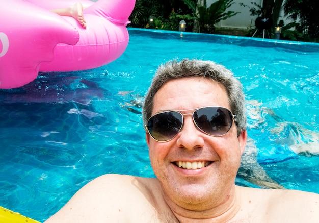 Mens met zonnebril die in een pool drijft