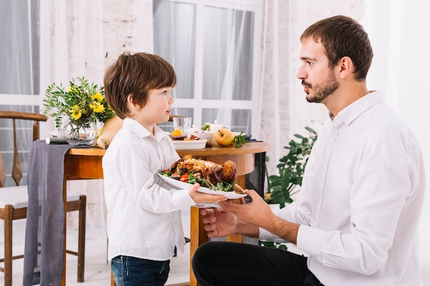 Mens met zoon die gebakken kip op plaat houdt
