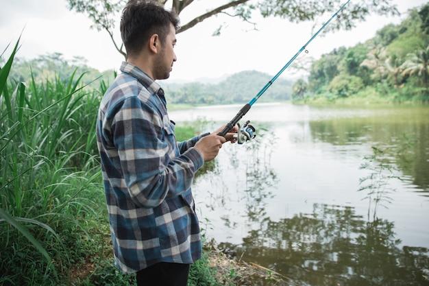 Mens op de rivieroever visserijvissen