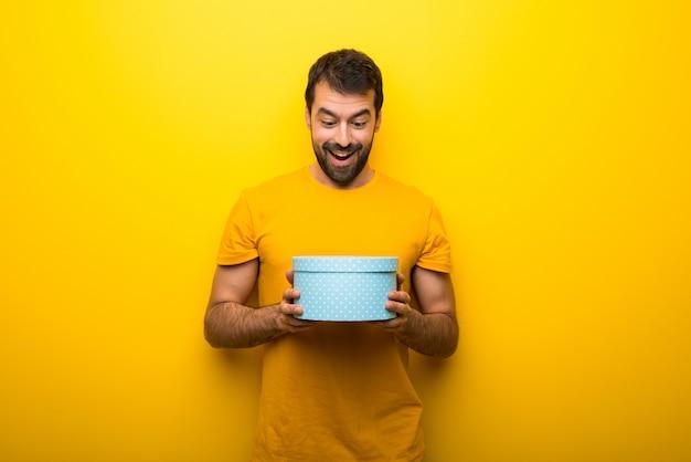 Mens op geïsoleerde trillende gele de giftdozen van de kleurenholding in handen