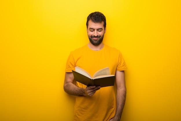 Mens op geïsoleerde trillende gele kleur die een boek houdt en van het lezen geniet