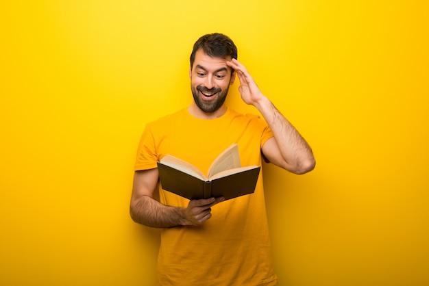 Mens op geïsoleerde trillende gele kleur die een boek houdt en verrast terwijl het genieten van van lezing