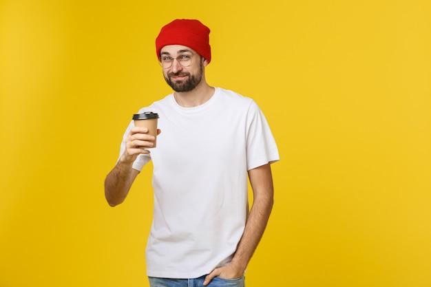 Mens op geïsoleerde trillende gele kleur die een koffie in meeneemdocument kop nemen en glimlachen omdat hij de dag goed zal beginnen.