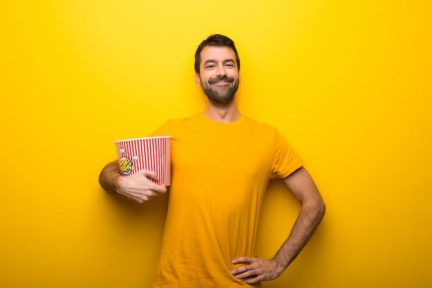 Mens op geïsoleerde trillende gele kleur die popcorns eet