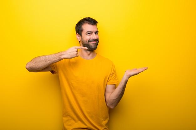 Mens op geïsoleerde trillende gele kleurenholding copyspace denkbeeldig op de palm om een advertentie op te nemen