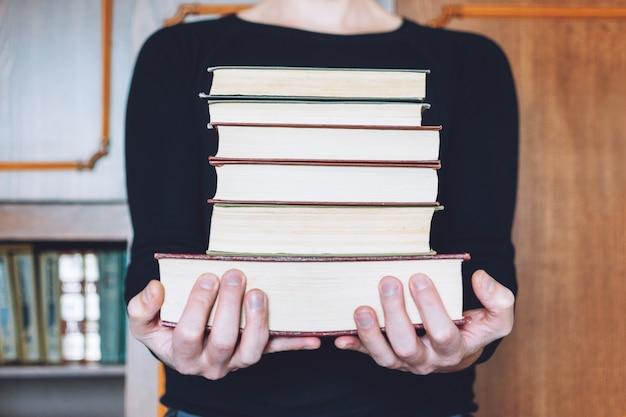 Mens, student die vele boeken in handen houdt