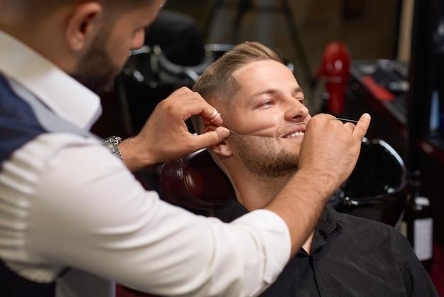 Mens tijdens procedure van het inpassen van baard in kapperswinkel