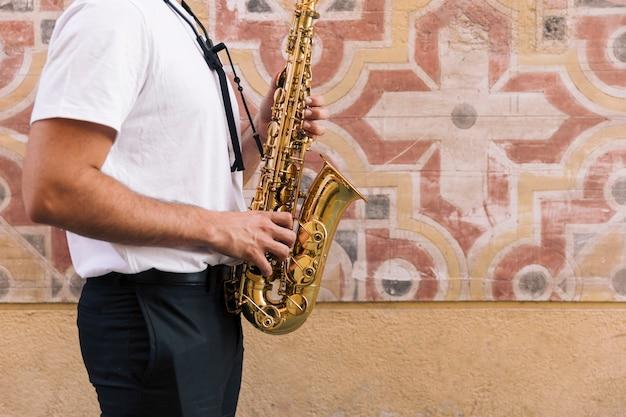 Mens zijdelings de saxofoon met geometrische achtergrond spelen