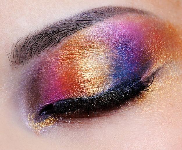 Menselijk gesloten oog met veelkleurige oogschaduw - macrospruit