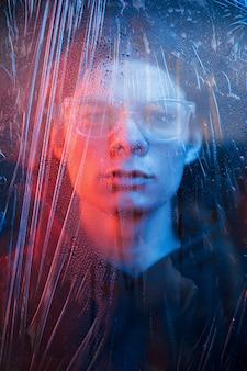 Menselijk gezicht achter het glas. studio opname in donkere studio met neonlicht. portret van ernstige man achter het natte glas