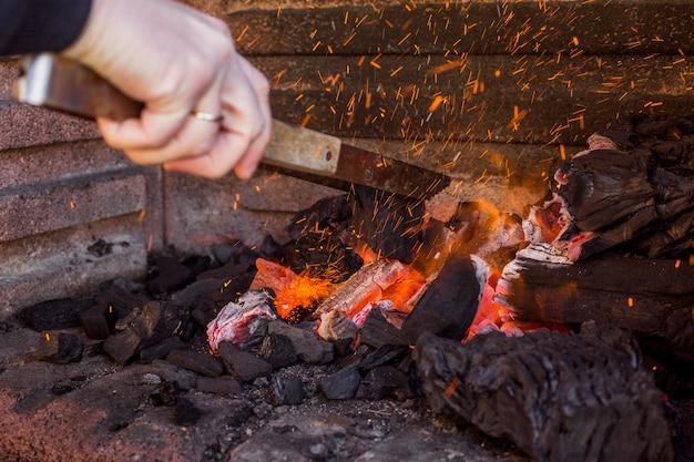Menselijk hand brandend hout in vuurplaats