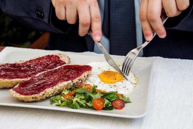 Menselijk hand snijdend ei tijdens ontbijt