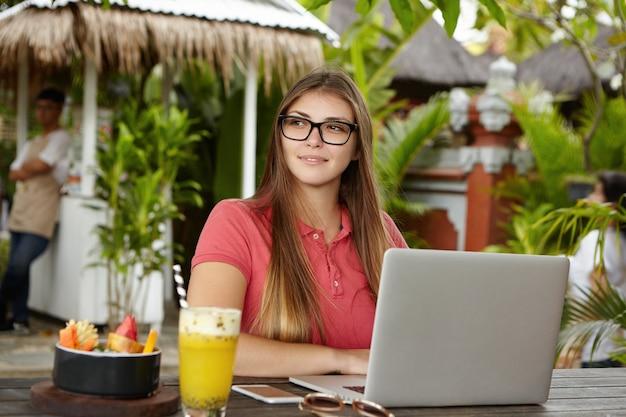 Menselijk, modern technologie- en communicatieconcept. aantrekkelijke zakenvrouw in stijlvolle glazen zit open laptop aan houten tafel met cocktail, fruitschaal