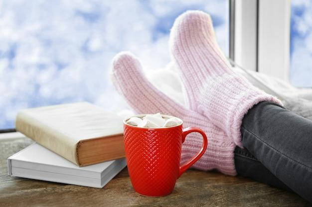 Menselijke benen in gebreide sokken op vensterbank naast kopje koffie en boeken