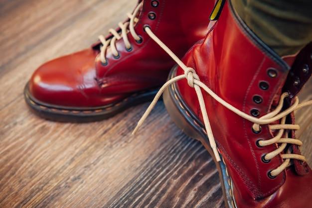 Menselijke benen in stijlvolle felrode laarzen met dikke witte veters samengebonden op houten