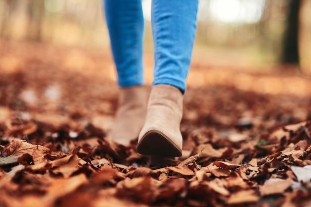 Menselijke benen lopen door herfstbladeren