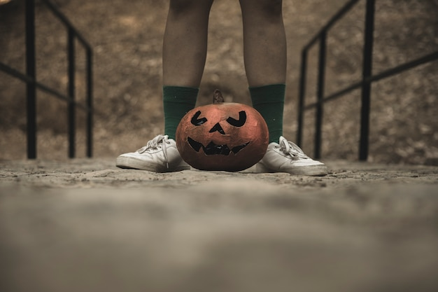 Menselijke benen met halloween-pompoen die op gangen in park wordt geplaatst