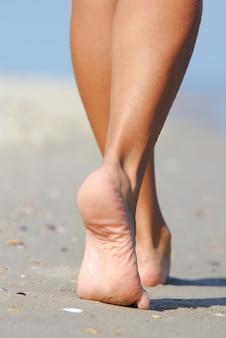 Menselijke benen. mooie vrouw die op het strand loopt