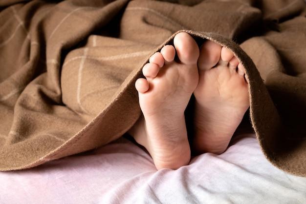 Menselijke blote voeten steken onder de deken vandaan