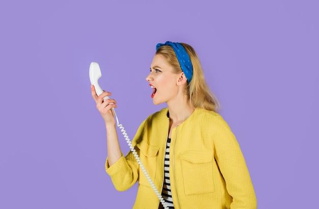 Menselijke emotie boos pinup meisje schreeuwen in handset schreeuwende vrouw met handset van vaste telefoon