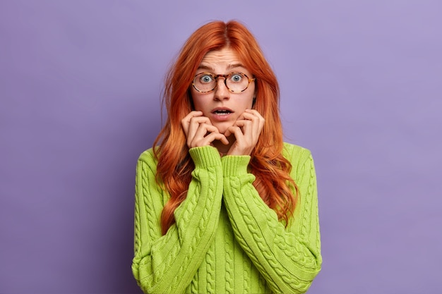 Menselijke emoties concept. emotionele bezorgde vrouw opent mond en voelt zich beschaamd bang om te zien dat iets de adem in houdt van verbazing draagt een groene trui.