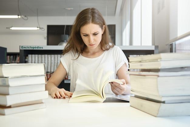 Menselijke emoties en gevoelens. beklemtoonde studentenvrouw die voor examens voorbereidingen treft, die bij bibliotheek voor grote stapels boeken bestudeert, die leerboek staart