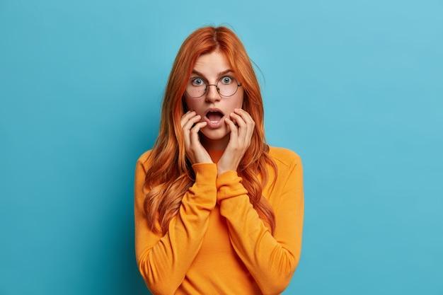 Menselijke emoties en gevoelens concept. sprakeloze roodharige vrouw houdt handen in de buurt van geopende mond reageert op schokkend nieuws, vraagt zich af, gekleed in casual trui.