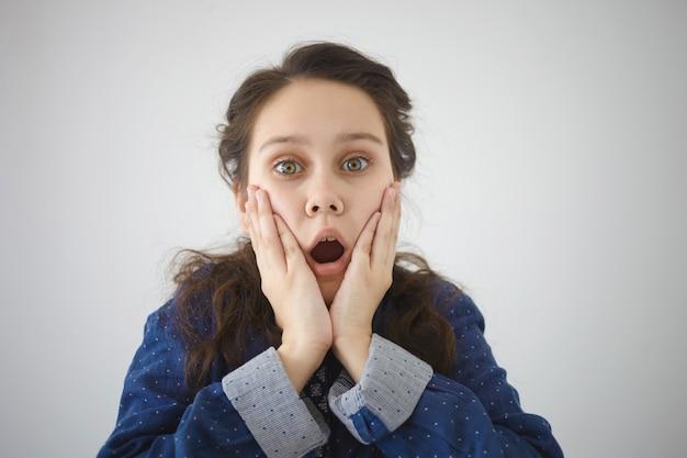 Menselijke emoties, gevoelens, reactie en houding. horizontaal schot van verbaasde vrouwelijke tiener die mond wijd opent en haar wangen vasthoudt