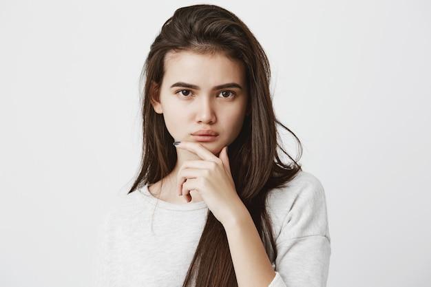 Menselijke emoties, gevoelens, reactie en houding. mooie vrouw in casual t-shirt met lang donker steil haar, houdt de hand op de kin in twijfel en achterdocht, sceptisch over iets